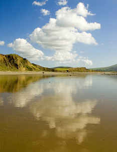 reflections of the clouds on a wet beach, Dinas Dinlle beach, North Wales UK