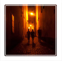 Three in a street, three people walking down a side street in Prague at night