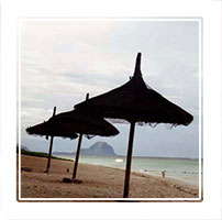 sun umbrellas on the beach in Flic en Flac, on the west coast of Mauritius in the Indian Ocean