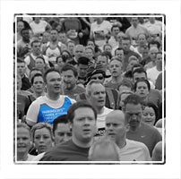 Selective colour photograph highlighting a single runner who is representing a charity for Parkinsons disease at the Manchester 10K run