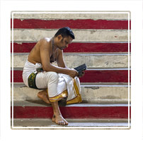 'Social Media Monk', a Hindu preacher reading his socialmedia news on his smartphone whilst cooling down in the Batucaves  in the north of Kuala Lumpur Malaysia