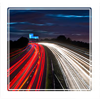 trailing lights, cars streaming past on the M56 at dusk, a motorway in Cheshire England