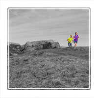 A selective colour photograph of two runners training in DErbyshires Peak district national park