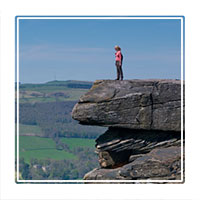 livin' edge, a woman stands on thge edge of a rock formation in the Derbyshire Peak district national park, England