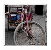 A rusty but trusty tricycle in teh courtyard of a Chinese family